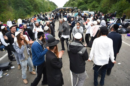 Jewish pilgrims dance as they gather on the Belarus-Ukraine border, in Belarus, Tuesday, Sept. 15, 2020. About 700 Jewish pilgrims are stuck on Belarus' border due to coroavirus restrictions that bar them from entering Ukraine. Thousands of pilgrims visit the city each September for Rosh Hashana, the Jewish new year. However, Ukraine closed its borders in late August amid a surge in COVID-19 infections. (TUT.by via AP)