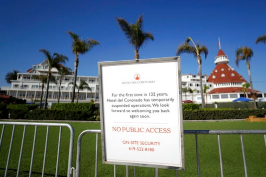 FILE - In this June 11, 2020 file photo a sign informing passersby of the hotel's closure is posted outside the Hotel Del Coronado in Coronado, Calif. California's unemployment rate has fallen to 11.4% in August. The Employment Development Department says the state added 101,900 jobs in August. Most of those were government jobs, including temporary positions for the U.S. Census. California lost more than 2.6 million jobs in March and April because of the coronavirus. (AP Photo/Gregory Bull, File)