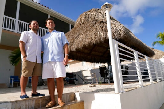 Freddy Vallejo Jr., right, poses for a photograph with his brother Joel, Saturday, Sept. 26, 2020, at the family vacation home in Key Largo, in the Florida Keys. Their grandfather Jorge Vallejo, a retired OB-GYN, and uncle Carlos Vallejo, who practiced internal medicine, died of the coronavirus within weeks of one another in South Florida. (AP Photo/Lynne Sladky)