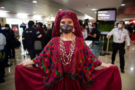 A model from the Guatemalan Tourism Institute poses for photographers wearing an indigenous ceremonial costume during the reopening of La Aurora International Airport in Guatemala City, Friday, Sept. 18, 2020. Guatemala reopened its borders Friday, and is allowing commercial flights from La Aurora that had been restricted to humanitarian and cargo flights since closing its borders in March due to the COVID-19 pandemic. (AP Photo/Moises Castillo)