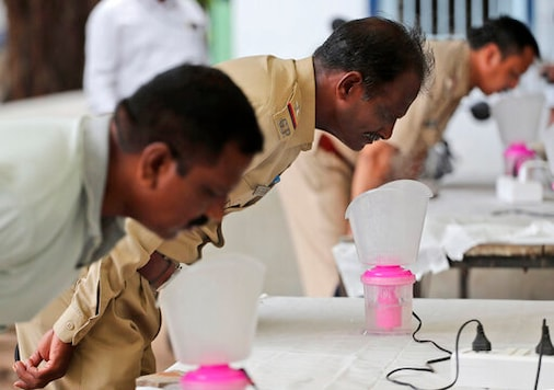 Indian policemen inhale steam at steam stations set up outside the office of the Commissioner of Police as a precautionary measure against the coronavirus in Ahmedabad, India, Saturday, Sept. 26, 2020. The nation of 1.3 billion people is expected to become the pandemic's worst-hit country within weeks, surpassing the United States. (AP Photo/Ajit Solanki)