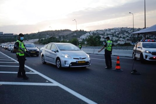 Israeli police officers check cars at a checkpoint during a three-week lockdown near Jerusalem, Sunday, Sept. 20, 2020. Israel went back into a full lockdown to try to contain a coronavirus outbreak that has steadily worsened for months. (AP Photo/Sebastian Scheiner)