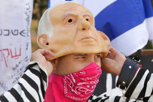 A protester wears a bandana as a face mask as he pulls on a rubber mask representing Israeli Prime Minister Benjamin Netanyahu outside of the Knesset in Jerusalem, Thursday, Sept. 24, 2020, after Israel moved to further tighten its second countrywide lockdown as coronavirus cases continue to soar. Prayers during the ongoing Jewish High Holidays, as well as political demonstrations, would be limited to open spaces and no more than 20 people, and participants would have to remain within the restricted distance from home. (AP Photo/Maya Alleruzzo)