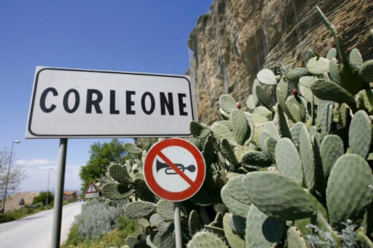 FILE -- In this file photo taken on April 12, 2006, a road sign announces the town of Corleone, Italy. The Sicilian town of Corleone, made famous by the fictional Mafia clan in The Godfather, has ordered schools closed and a limited lockdown after a spate of coronavirus infections were tied to a big wedding there last week. (AP Photo/Luca Bruno)