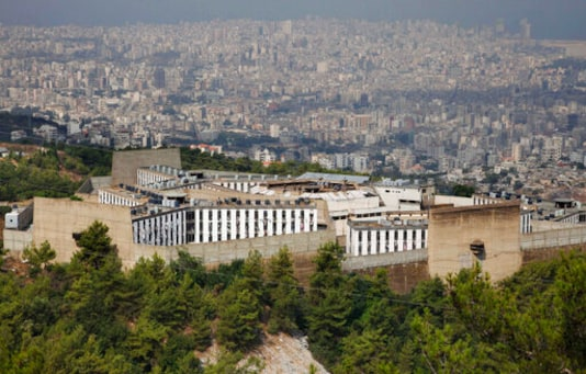 FILE - This Aug. 18, 2009 file photo, shows Roumieh Prison, in the Beirut suburb of Roumieh, Lebanon. The head of the country's doctors union warned Thursday, Sept. 17, 2020 that Roumieh, Lebanon's largest prison, is witnessing an alarming spread of coronavirus cases with more than 200 detainees testing positive recently and more could get the infection as many of them are not abiding by preventive measures. (AP Photo/Bilal Hussein, File)