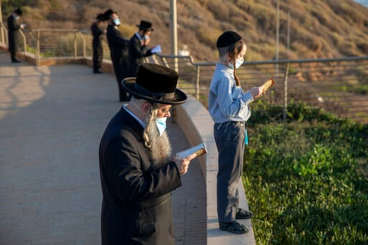 Ultra-Orthodox Jews of the Kiryat Sanz Hassidic sect pray on a hill overlooking the Mediterranean Sea as they participate in a Tashlich ceremony during a nationwide three-week lockdown to curb the spread of the coronavirus in Netanya, Israel, Thursday, Sept. 24, 2020. Israel moved to further tighten its second countrywide lockdown as coronavirus cases continued to soar. (AP Photo/Ariel Schalit)