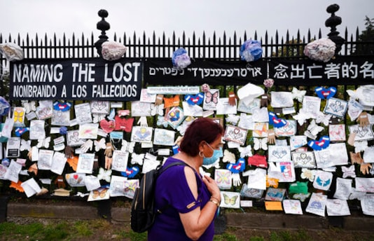 FILE - In this May 28, 2020, file photo, a woman passes a fence outside Brooklyn's Green-Wood Cemetery adorned with tributes to victims of COVID-19 in New York. The U.S. death toll from the coronavirus topped 200,000 Tuesday, Sept. 22, a figure unimaginable eight months ago when the scourge first reached the worlds richest nation with its sparkling laboratories, top-flight scientists and towering stockpiles of medicines and emergency supplies. (AP Photo/Mark Lennihan, File)