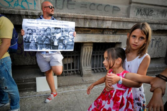 Children play next to a man holding a banner showing children in a concentration camp and a paraphrase from a statement by Romanian President Klaus Iohannis that reads