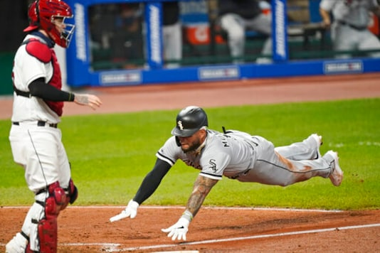 Chicago White Sox's Yoan Moncada, right, scores as Cleveland Indians' Roberto Perez stands near the plate during the seventh inning of a baseball game Thursday, Sept. 24, 2020, in Cleveland. (AP Photo/Tony Dejak)