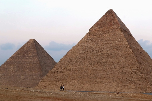 People walk in front of the Great Pyramids in Giza, on the outskirts of Cairo, Egypt. (Credit: REUTERS)