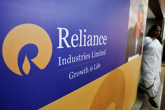 A woman walks past a poster of Reliance Industries installed outside the venue of the company's annual general meeting in Mumbai. (REUTERS/Vivek Prakash/File Photo)