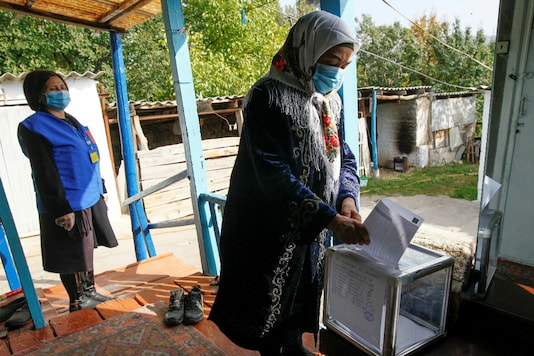A woman casts a ballot at home during a parliamentary election in the village of Arashan, Kyrgyzstan, October 3, 2020. REUTERS/Vladimir Pirogov