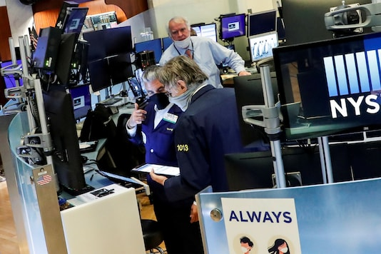 Traders wearing masks work, on the first day of in person trading since the closure during the outbreak of the coronavirus disease (COVID-19) on the floor at the New York Stock Exchange (NYSE) in New York, U.S., May 26, 2020. REUTERS/Brendan McDermid/File Photo
