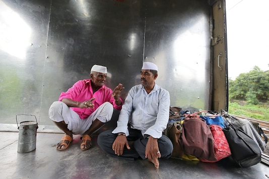 FILE PHOTO: Dabbawalas, also known as tiffin carriers, wearing traditional caps travel in a train in Mumbai, India, September 19, 2018. (REUTERS)