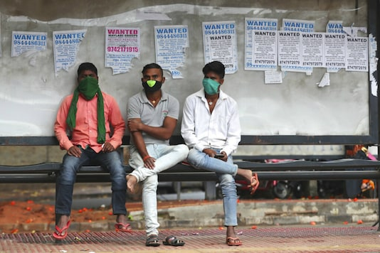 People in masks wait at a bus stop in Bengaluru. (AP)