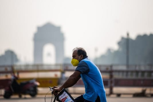 A cyclist rides past India Gate amid smoggy condition in New Delhi on Tuesday. (AFP)