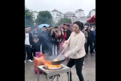 The woman is seen grooving to the 2012 hit song as she stir fries the noodles and a crowd is gathered around her.