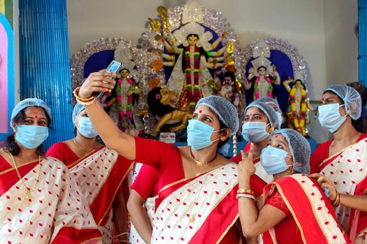 South Dinajpur: Women take a selfie in front of the idol of Goddess Durga after West Bengal Chief Minister Mamata Banerjee virtually inaugurated their community Durga Puja, at Balurghat in South Dinajpur district, Wednesday, Oct. 14, 2020. (PTI Photo)(