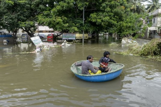 Workers use a boat to evacuate residents on a flooded street in Hyderabad on Thursday. (AFP)
