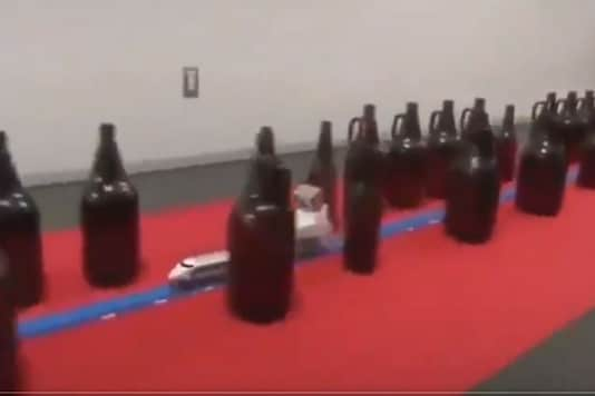 Toy train moving through glass bottles in viral video.