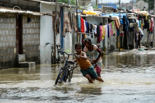 Children push a bicycle on a flooded street following heavy rains in Hyderabad on Thursday. (PTI)