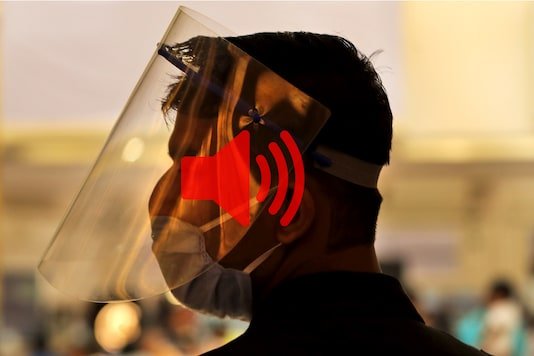 An employee of the PVR cinemas with a face shield and a mask stands at the entrance to welcome people in New Delhi, on October 15, 2020. (AP Photo/Manish Swarup)