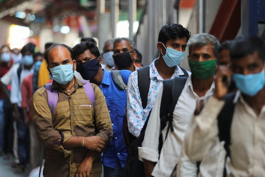 Passengers wearing protective face masks stand in a queue on a platform to get tested for the coronavirus disease, at a railway station, in New Delh. (Reuters)