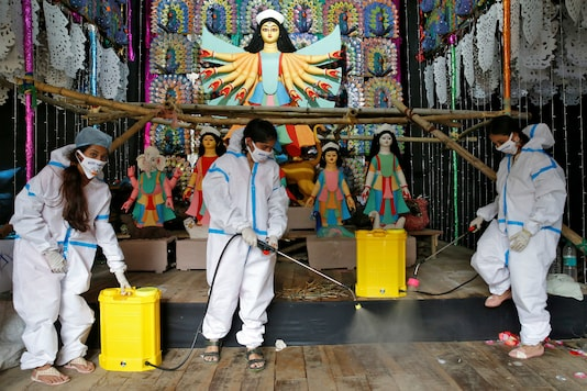 Women wearing PPE suits sanitize a pandal in Kolkata. (Reuters)