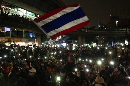 Pro-democracy protesters wave Thailand's national flag as others shine their mobile phone lights during an anti-government protest in Bangkok, Thailand, Sunday, Oct. 18, 2020. Thai police on Sunday declined to say whether they were taking a softer approach toward student anti-government demonstrations, after several mass rallies attracting thousands of protesters ended peacefully in Bangkok on Saturday. (AP Photo/Sakchai Lalit)
