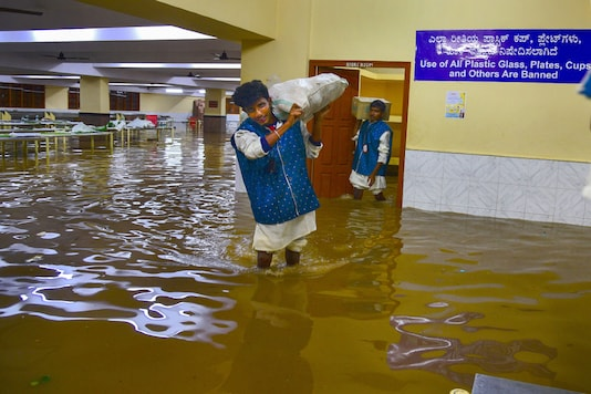 A worker carrying a sack wades through the waterlogged basement of a marriage hall in Bengaluru on Wednesday. (PTI)