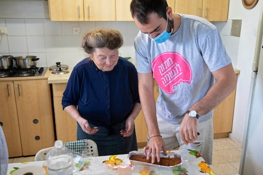 Sonia Rozenblatt, 85, tastes a cake made for her by Israeli volunteer Din Belz in the central Israeli city of Ra'anana. (AP Photo/Sebastian Scheiner)