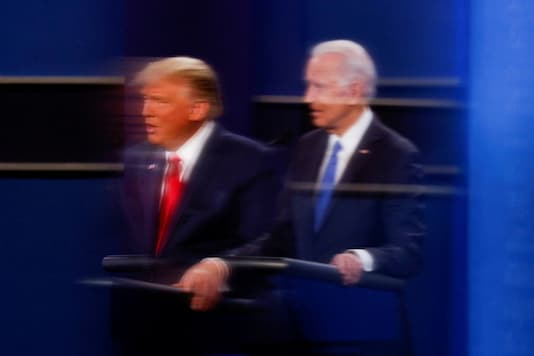 U.S. President Donald Trump and Democratic presidential nominee Joe Biden are reflected in the plexiglass protecting a tv camera operator from coronavirus as they participate in their second 2020 presidential campaign debate at Belmont University in Nashville, Tennessee, U.S., October 22, 2020. REUTERS/Mike Segar