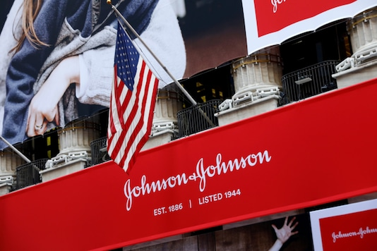 The US flag is seen over the company logo for Johnson & Johnson to celebrate the 75th anniversary of the company's listing at the New York Stock Exchange (NYSE), on September 17, 2019. (REUTERS/Brendan McDermid/File Photo)