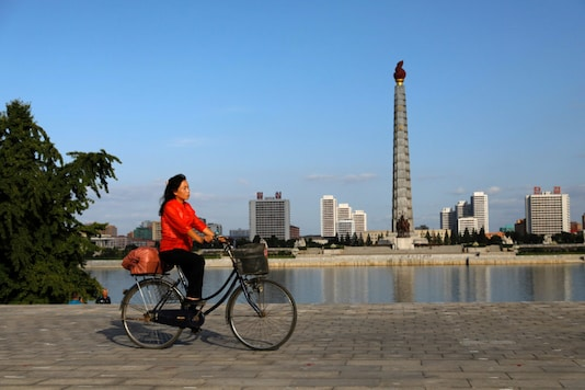 A woman rides a bicycle as Juche Tower is seen in the background along the Taedong river in Pyongyang, North Korea. (REUTERS/Danish Siddiqui/File Photo)