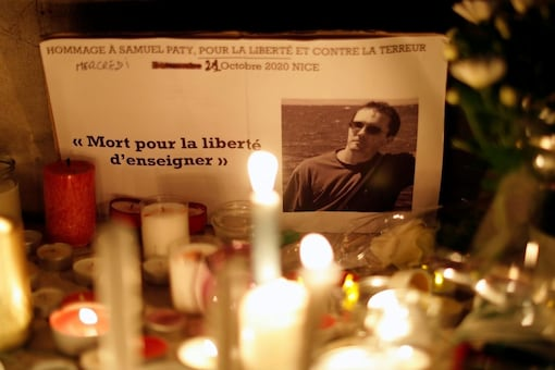 Candles are lit at a makeshift memorial as people gather to pay homage to Samuel Paty, the French teacher who was beheaded on the streets of the Paris suburb of Conflans-Sainte-Honorine, as part of a national tribute, in Nice, France, October 21, 2020. REUTERS/Eric Gaillard