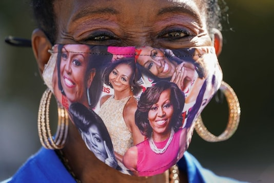 A woman wears a Michelle Obama face mask while waiting to cast her ballot as early voting begins at Mason District Governmental Center in Annandale, Virginia, U.S., October 14, 2020. REUTERS/Kevin Lamarque