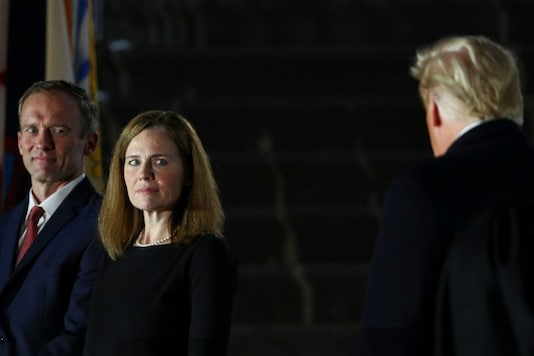 For representation: Judge Amy Coney Barrett and her husband Jesse Barrett look over at U.S. President Donald Trump after she was sworn in to serve as an associate justice of the U.S. Supreme Court on the South Lawn of the White House in Washington, U.S., October 26, 2020. REUTERS/Tom Brenner