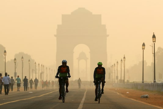 Two men cycle in front of India Gate which is shrouded in smog (Reuters)