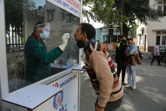 A health worker collects a nasal swab sample to test for Covid-19 at a government hospital. (AP Photo)