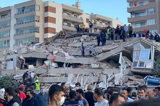 Rescue workers and local people try to save residents trapped in the debris of a collapsed building, in Izmir, Turkey, Friday, Oct. 30, 2020. (AP Photo/Ismail Gokmen)
