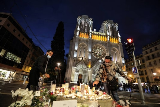 People light candles outside the Notre-Dame de l'Assomption Basilica in Nice on October 30, 2020, a day after a knife attacker killed three people. (Photo by Valery HACHE / AFP)
