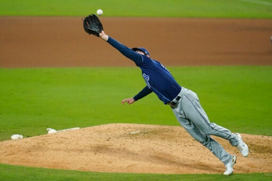 Tampa Bay Rays' pitcher John Curtiss reaches out to catch an infield hit by Houston Astros' Yuli Gurriel during the seventh inning in Game 3 of a baseball American League Championship Series, Tuesday, Oct. 13, 2020, in San Diego. (AP Photo/Gregory Bull)