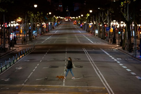 A resident walks with a dog on an empty street after curfew in Barcelona on Sunday, Oct. 25, 2020. Spain orders nationwide curfew to stem worsening outbreak. Spanish Prime Minister Pedro Snchez has declared a second nationwide state of emergency in hopes of stemming a resurgence in coronavirus infections. (AP Photo/Emilio Morenatti)