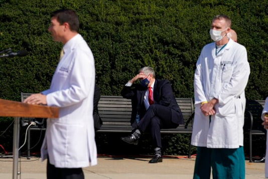 White House Chief of Staff Mark Meadows, seated center, listens as Dr. Sean Conley, physician to President Donald Trump, briefs reporters at Walter Reed National Military Medical Center in Bethesda, Md., Sunday, Oct. 4, 2020. Trump was admitted to the hospital after contracting the coronavirus. (AP Photo/Jacquelyn Martin)