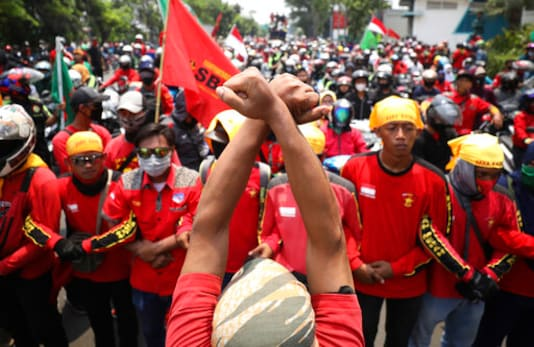 A labor demonstrator raises his fists in support of the protest against a controversial omnibus bill on job creation in Tangerang, Indonesia, Wednesday, Oct. 7, 2020. Thousands of students and laborers protested on Wednesday against the new law they say cripples labor rights and harms the environment. (AP Photo/Dita Alangkara)