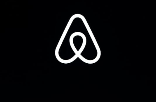 FILE - This Feb. 22, 2018, file photo shows an Airbnb logo during an event in San Francisco. Airbnb is setting up an endowment fund to support its hosts as part of its upcoming initial public offering. The San Francisco-based home-sharing company said it will set aside 9.2 million shares for the endowment, which will start funding projects when its value tops $1 billion. Airbnb has named a 15-member council of hosts that will meet monthly with Airbnb leadership and decide which projects to fund. (AP Photo/Eric Risberg, File)