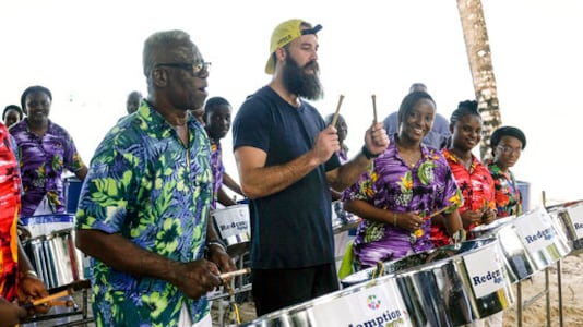 In this 2018 photo provided by CBS, professional volleyball player Maddison McKibbin, center, participates at an event in Trinidad and Tobago. Maddison McKibbin and his brother Riley McKibbin will be competing on The Amazing Race travel challenge reality show that premiers for its 32nd season on Oct. 14, 2020. (Timothy Kuratek/CBS via AP)