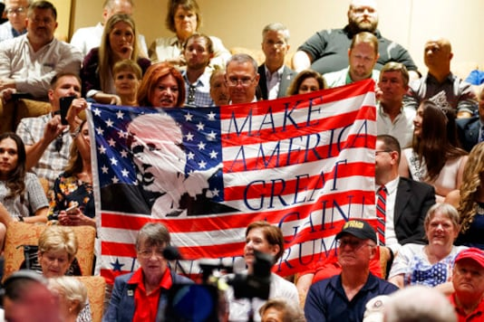 FILE - In this Thursday, Oct. 3, 2019 file photo, supporters of President Donald Trump hold a flag before he arrives to deliver remarks on Medicare at the Sharon L. Morse Performing Arts Center in The Villages, Fla. (AP Photo/Evan Vucci)