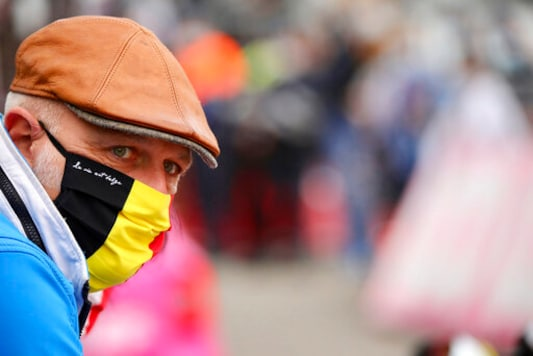 A spectator wears a protective mask as he watches the Belgian cycling classic and UCI World Tour race Fleche Wallonne, in Huy, Belgium, Wednesday, Sept. 30, 2020. (AP Photo/Olivier Matthys)