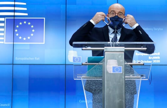 European Council President Charles Michel puts on his protective face mask after speaking during a media conference at an EU summit in Brussels, Thursday, Oct. 15, 2020. European Union leaders met in person for the first day of a two-day summit, amid the worsening coronavirus pandemic, to discuss topics ranging from Brexit to climate and relations with Africa. (Kenzo Tribouillard, Pool via AP)